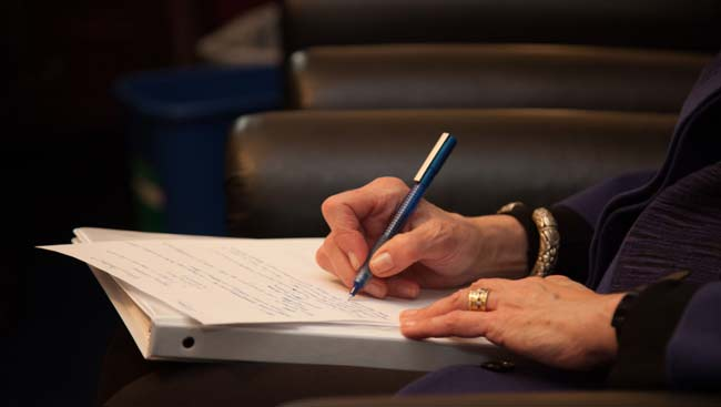 A hand writes notes during a lecture.
