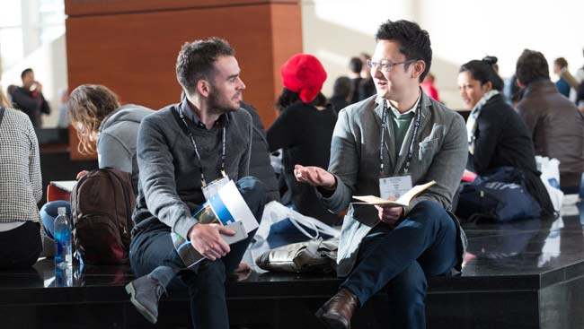 Two male neuroscientists network at a conference.