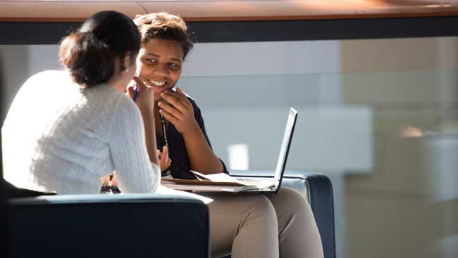 Two females share ideas about what to include on a CV.