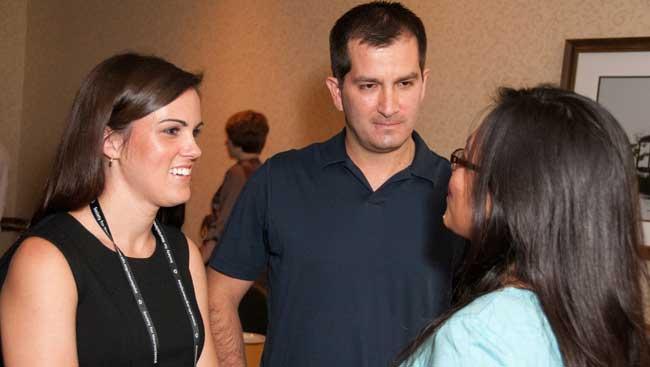 Three neuroscientists network at an event.