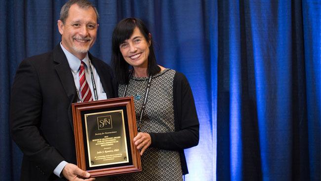 Julio Ramirez accepts award from Mara Dierssen