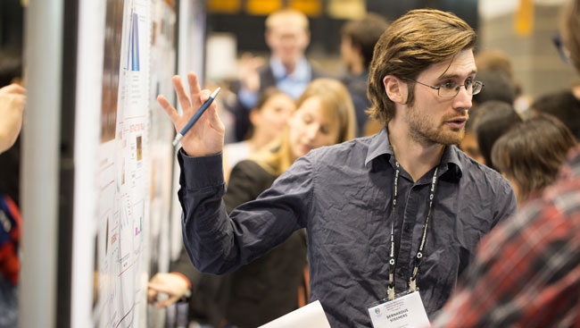 A male neuroscientist explains his research at a conference.