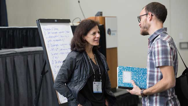 Two researchers have a discussion after a lecture.