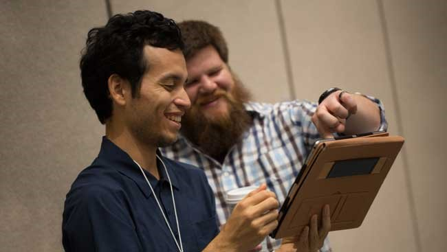 Two neuroscientists share data at a conference.