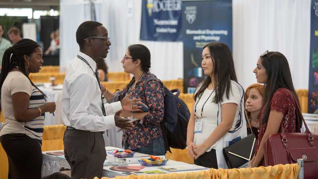 Neuroscientists network at a graduate school fair.