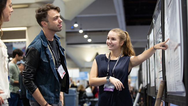 Presenter discussing on the poster floor at Neuroscience 2018.