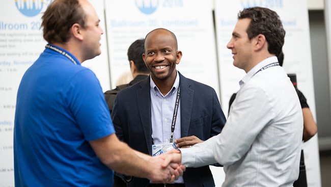 Attendees shaking hands at Neuroscience 2018.