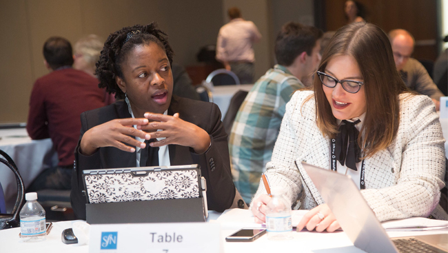 Attendees discussing at a table at SfN's annual meeting