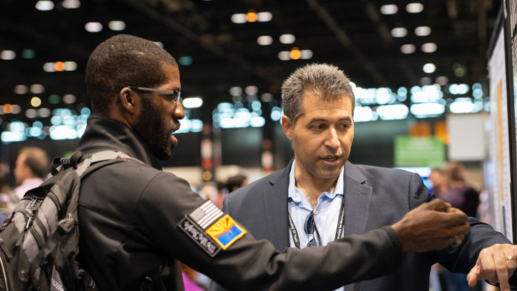 Two men discuss a poster at Neuroscience 2019