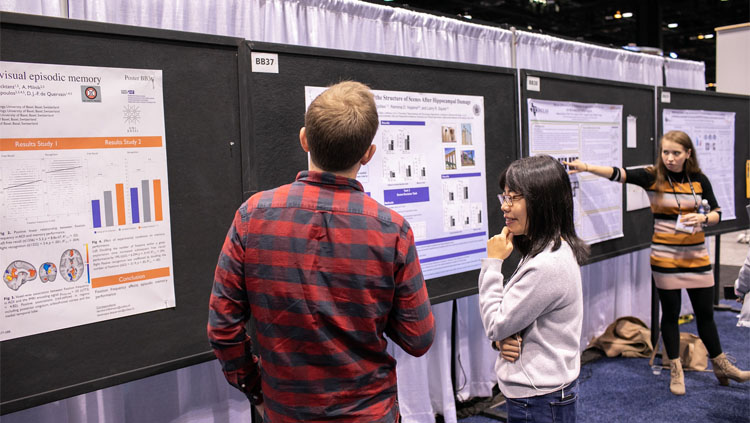 A women in a grey sweater presents her poster to a man in a red and grey plaid shirt at Neuroscience 2019