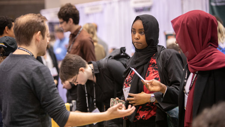 A man has a discussion with two women at the Neuroscience 2019 Graduate School Fair.