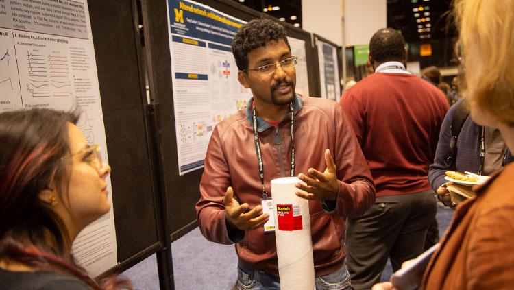 Three neuroscientists discuss a scientific display on the poster floor at Neuroscience 2019