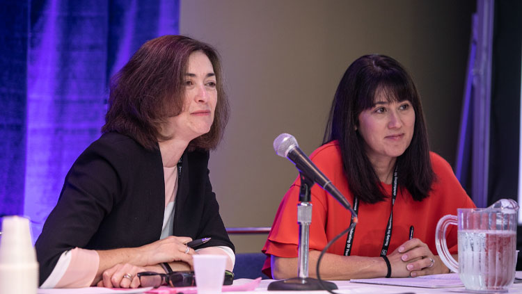 Two panelists listen intently while sitting at a table at a professional development workshop at Neuroscience 2019.