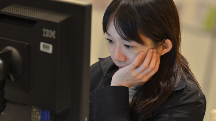 A woman stares intently at a computer.