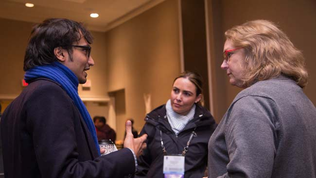 Two female and one male scientist network at a conference.