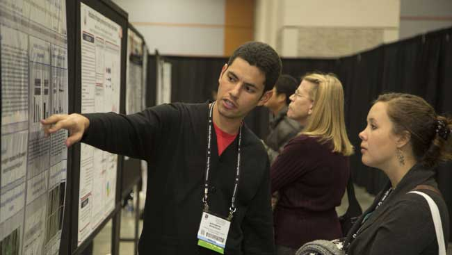 A poster presenter explaining his research to an annual meeting attendee