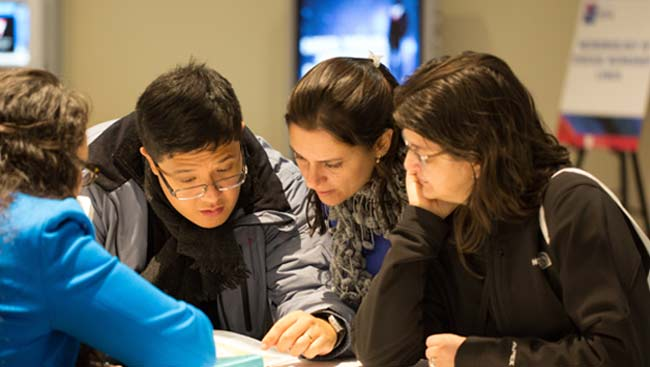 A group of neuroscientists look at a helpful resource together.
