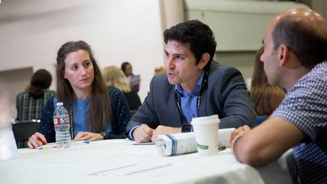 Female and male neuroscientists share ideas at a networking event.