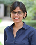 Headshot of Aparna Shah standing outside wearing a navy blue button up shirt.