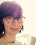 Headshot of April Clyburne Sherin wearing red glasses.