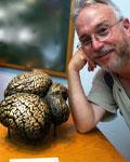 Image of Bill Grisham next to a brass statue of a brain.