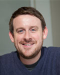 Headshot of Ian Maze wearing a blue sweater