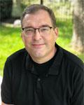 Headshot of Jim Newman wearing a black shirt.