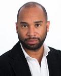 Headshot of Mathew Abrams wearing a white button down shirt with a black jacket.
