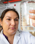 Naomi Lee examines the contents of a beaker. Photo taken by NAU Marketing.