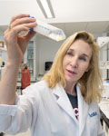 Image of Sheena Josselyn holding a test tub wearing a lab coat.