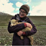Image of Lara Rogerson-Wood standing in a field holding a goat.