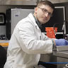 Image of Zackary Bowers in a lab coat working.